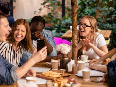 sincere-laugh-showing-picture-smartphone-casual-meeting-with-best-friends-restaurant-terrace_8353-10272